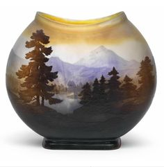 A vase featuring a mountainous lakeside landscape,  Gallé, Nancy, c. 1925, the colourless glass partially cased in ochre yellow, overlaid in pale violet and dark brown and decorated with an acid etched mountainous lakeside landscape, the lentoid body supported on a rectangular foot, with raised signature Gallé in the lake, height 23.5 cm,