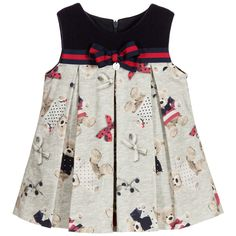 Pretty, empire line dress by Lapin House, made with a soft brushed cotton and wool blend. The navy blue, cotton jersey bodice has a red and navy blue grosgrain trim with a bow appliqué and the designer's silver metal logo charm. The skirt has a lovely teddy bear print, with box pleats at both the front and back. Fully lined in soft cotton, the dress fastens with a concealed zip at the back and would look great with red shoes.
