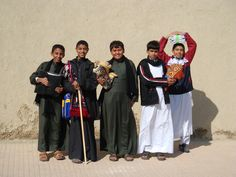 Students walking home from school for lunch and prayer time, with books wrapped in prayer rugs. al-Hasa, Saudi Arabia   (Photo Credit: Michael-Ann Cerniglia)