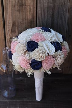 Thank you for looking. I hope to work with you on your floral needs. This listing features a bouquet features shell flowers, roses, mums, carnations and zinnias in English navy, rosy pink, champagne, and cream. This bouquet has cream filler and is wrapped in cream fabric and accented with a lace collar with pearls. Any of these flower colors may be hand dyed in your very special wedding palette colors. The first 3 pictures above shows a large size. It measures 28 inches around the whole…