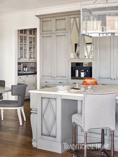 Custom glazed gray cabinets feature a diamond motif. Cabinet doors to the left of the built-in Miele coffeemaker slide back to reveal the TV.  - Photo: Emily Jenkins Followill / Kitchen Design: Mary Kathryn Timoney