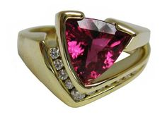 This 18K yellow gold ring by artist Tom Dailing shows off a trilliant, concave-cut pink tourmaline, accented by white diamonds.