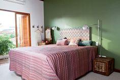No quarto do casal, a parede na cor cactus, da Suvinil, ganha movimento com a estampa da cabeceira Missoni Home em tons lavados. roupa de cama e almofadas da mesma marca. Ganchos da Tok & Stok. a penteadeira de madeira completa o clima