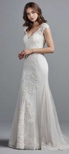 This elegant sheath wedding gown features crosshatched tulle, Swarovski crystals, and beaded lace appliqués accenting the illusion cap-sleeves, illusion back, and illusion petal-shaped train. Complete with V-neckline, and lined with Inessa Jersey for a luxe fit. Finished with covered buttons and zipper closure.