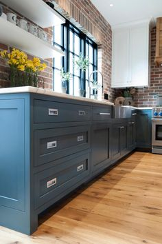 Modern cabinets and stainless steel appliances give the original exposed brick and hardwood floors an updated look.