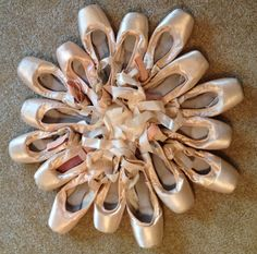 Wall art made from old pointe shoes.. Hot glue them onto a wire wreath form and hang!