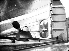 The Titanic in dry dock. Here you can see the scale of the person standing next to one of the propellers, 1912.