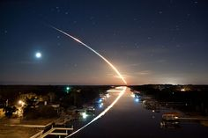 Space shuttle Endeavour STS-130 launches into orbit toward the east, as the stars and waning crescent moon trail toward the west, leaving a beautiful reflection on the Intracoastal Waterway in Ponte Vedra, Florida.