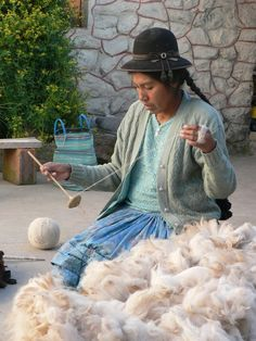 Péru, on the edge of lake Titicaca, woman preparing wool of the alpaca to weave.