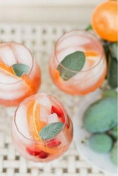 Custom wedding cocktail with oranges, mint, berries etc. Love the coral green and red color palette!
