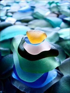 These are bits of sea glass. Sea glass or beach glass is physically and chemically weathered glass is found on beaches along bodies of fresh and salt water. These weathering processes produce natural frosted glass. Many beachcombers collect sea glass as a hobby and for use in jewelry.