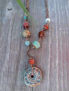 Teal Blue Green and Rust Red Sun Wheel Pendant with Ceramic and Stones. $36.00, via Etsy.