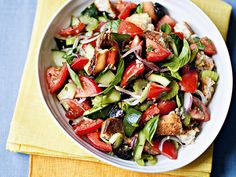 Panzanella salad in white bowl on yellow cloths