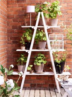 White pot stand with uniform pot plant containers...looks nice against the brick wall.