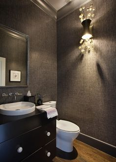With its carbon-gray grass cloth wall covering (part of the Glam Grass collection from Phillip Jeffries), this powder room has a sleek, sexy feel