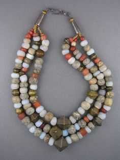 Opalescent moon beads from Venice and Bohemia, traded in Africa in the century, antique Africa carnelians, prehistoric woolly mammoth bone beads, and antique Yoruba brass bicone beads from Nigeria. Raw Gemstone Jewelry, Beaded Jewelry, Silver Jewelry, Handmade Jewelry, Jewelry Necklaces, Beaded Necklace, Unique Jewelry, Jewelry Ideas, Jewellery
