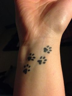 Dog paw memorial tattoo maybe with a heart tracing through behind.