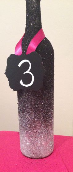 Ombre glittered wine bottle table number or centerpiece.  www.thefinaltouchevents.com