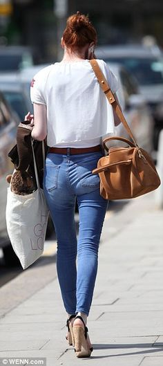 Satchel chic: Eleanor swung a brown leather bag from her shoulder as she walked down the s...