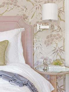 lovejoy design bedroom: lilac upholstered headboard with contrast piping, patterned wallpaper, sconce