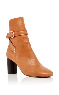 These **Isabel Marant** boots are crafted in tan calf leather with a wrap around buckle strap. The chunky, cylindrical heel in dark brown finishes this design with the perfect contrast.