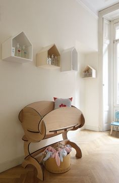 Modern design style crib paired up with hanging shelves shaped like houses painted in pastel colors gives this nursery decor a slightly retro feel. #nurserydecorideas