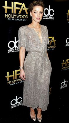 AMBER HEARD in a shimmery gold midi dress, which she accessorizes with matching nude pumps and delicate gold jewels