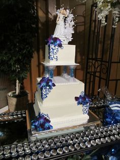 3 Tier Blue and White Square Wedding Cake  -  Groom picked the topper, this is my first official wedding cake.  It is white cake with a cherry cream filling and a cream cheese frosting, pillar rocks to match the centerpieces
