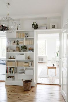 white built in shelving and storage. love the shelves above the door frame for extra organization.