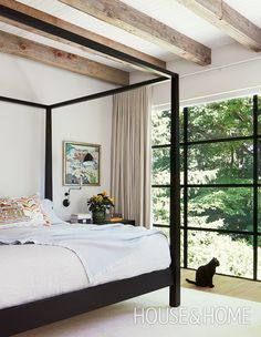 A black four-poster bed and the black-framed windows bring graphic definition to this principal bedroom.   Photographer: Virginia Macdonald   Designer: Connie Braemer