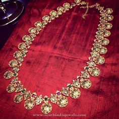 22 carat gold antique finish peacock haram adorned with Ram Sita coins and studded with rubies, emeralds and polki diamonds by Parnicaa Jewellers.