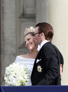 Newlyweds Princess Victoria of Sweden and Daniel Westling stand on the balcony of the Royal Palace of Stockholm with their guests and wave to the crowd.