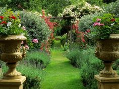Ornate Urns  Colorful flowers planted in large urns provide a stately frame for a grass walkway in this traditional garden.