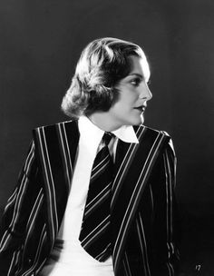 """""""Doris Nolan dines in this clever jacket of navy blue tie silk, gaily striped in red and white. Her four-in-hand of the same material is worn with a white crepe shirtmaker, decidedly masculine in design."""" 1936."""
