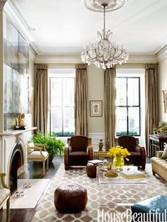 house beautiful traditionally elegant living room tan beige and white high ceilings crystal chandelier geometric rug
