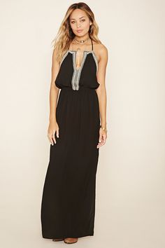 A maxi dress featuring a floral embroidery, M-slit front, keyhole neckline, cami straps with a T-strap back and an elasticized waist.