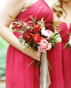 These red and pink bridesmaid bouquets, designed by Munster Rose, include ranunculus, dahlias, garden roses, nandina foliage, olive leaf, and nine bark.