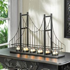 🌉 🏃 Golden Gate Candleholder  A candlelit accessory and a conversation starter, all in one!  This charming candle holder features six fluted clear glass candle cups set on the framework of a suspension bridge.  Metal posts, golden wires, and beaded details make this a lighting accent that is your room's bridge to style!  #CelestialDecor #FlorCarrasco #Onlineshop #HakeemAlexander #international #FortLauderdale #florida #goldengatebridge #candlelight #homedecor #officedeco