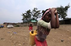 A congolese girl carries a jerry-can of water in Bunagana near the Uganda-Democratic Republic of Congo border