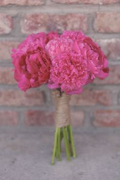 A bright pink peony bouquet wrapped with twine by Festive Designs.