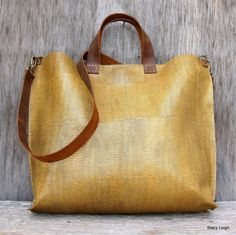 Simple leather tote bag made from a honey beige, lizard embossed leather. The leather is slightly stiff and keeps its shape, the color is wheat. The bag is unlined with 2 drop in pockets and a magnetic snap closure. The handles are short and rugged, made from mustang oiled cowhide leather in a distressed brown. The shoulder strap is detachable and long enough to use cross body style. The bag is 18 across the top, 14.5 across the bottom and 13 deep. The bag has a very organic look and feel.