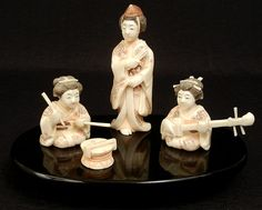 """Three small carved ivory figurines, one of a woman playing the drums, one of a woman playing the mandolin, and on of a woman standing holding a fan in her hands, signed on bottom, on wooden stand, tallest is 4 1/4"""" high"""