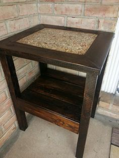 Plant stand by the front door. Made from: Palletwood, granite scrap piece, grout and stain.