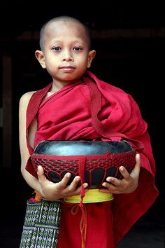 A Burmese novice (a child monk)  Morning food collection is every day routine for monks in Burma /Myanmar .