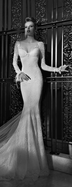 Galia Lahav Haute Couture - Bridal Gown - Eleanor is a long sleeve gown with a V-neck front. The back is a V-shape cut as well with lace embroidered flames facing inward. The lace flames travel from the shoulder line down to the train.