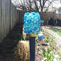 DIY Garden Art, it gives off a soft blue glistening glow at night thanks to the solar light inside. Should the light quit working, I can simple untwist it and replace the battery in the light.