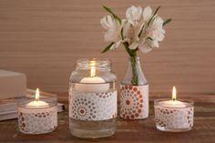 Os vidros de conservas viraram suporte para velas e a garrafinha d'água se transformou em um vaso de flores. As velas boiam no vidro com água. O detalhe que faz a diferença é a tira de papel decorativo em volta dos vidros.
