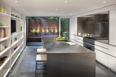 white linear kitchen + concrete floors + s/s counter + huge picture window glass