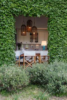 Vista desde el jardín hacia el comedor de una casa de fin de semana en Cardales. Afuera, una enredadera cubre las paredes; adentro, lámpara colgante hecha con fanales de hierro.