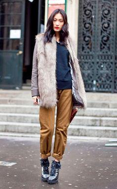 Street style look com colete de pêlo fake cinza, calça marrom e sapato preto.